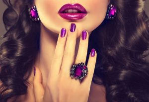 Beautiful girl showing purple manicure and stylish jewelry