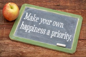 Make your own happiness priority - advice on a slate blackboard against red barn wood