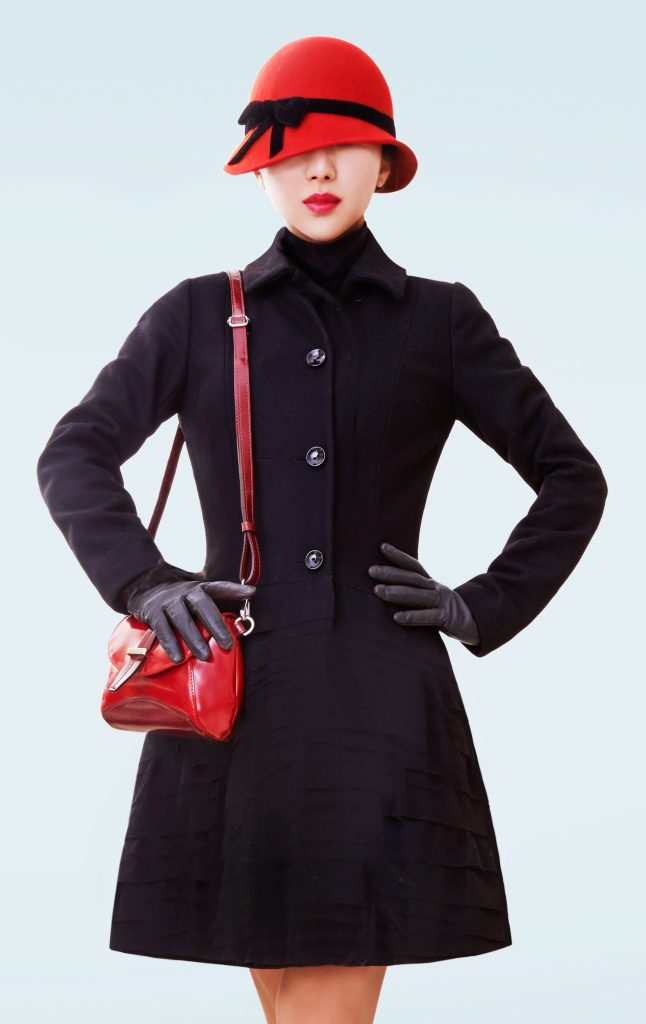 Winter Fashion look woman. Black coat, hat and handbag.isolated on light blue background.
