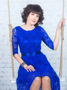 Young beautiful woman in blue dress sitting on swing background of white brick wall